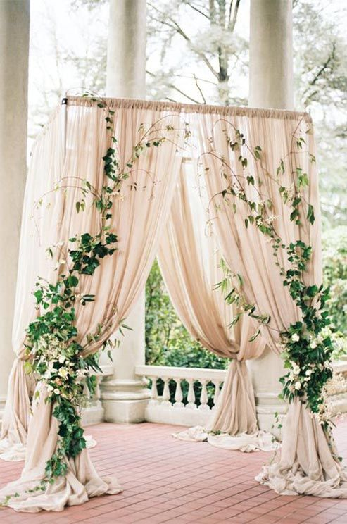 Ethereal sheer pink curtains covered in ivy vines create a romantic altar.