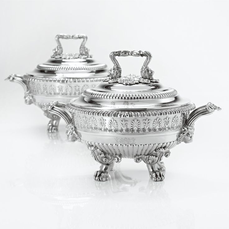 A Pair of Regency Silver Circular Sauce Tureens, Covers and Liners, Paul Storr, London, 1819  the bodies partly gadrooned and applied with band of stiff leaves and anthemia, engraved on both sides with contemporary arms and supporters, the reeded loop handles springing from lion heads and centered by shells, raised on four paw feet headed by classical foliage, the conforming covers with loop finails, engraved with hound and unicorn crests, removable liners with matching crests, fully marked,