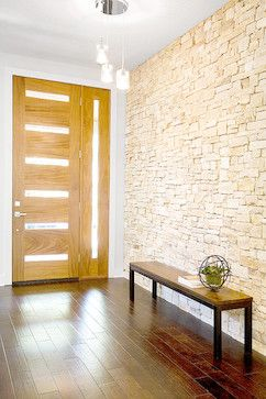contemporary entry with stone feature wall, timber flooring and modern entry door with side glass panel. Clean and uncluttered.