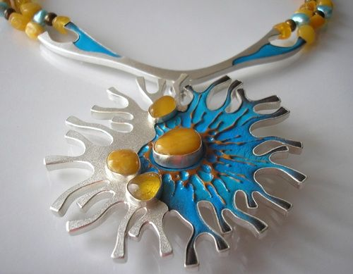 Brooch-necklace made of silver 930, leather, Baltic amber and pearl farms. The pendant is silver mold filled with hand-painted skin in summer colors - two shades of blue (cobalt and ultramarine blue) with orange-brown accents. Baltic amber nuggets put in the silver cargi. The pendant is suspended from a double strings of amber and pearl farms. Silver frosted, polished lipping. Diameter of pendant approx 7.5 cm, length measured from the inside of the necklace 43 cm.
