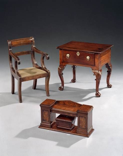 A GEORGE II MINIATURE LOWBOY. A REGENCY MINIATURE SIDEBOARD. A REGENCY CHILDREN'S ARMCHAIR. A GEORGE II ELM MINIATURE LOWBOY  An unusual early 18th century elm miniature lowboy, having a rectangular top with rounded edge above a single drawer with ring handles; on cabriole legs with shell carving to the knees terminating in pad feet.  English, circa 1730