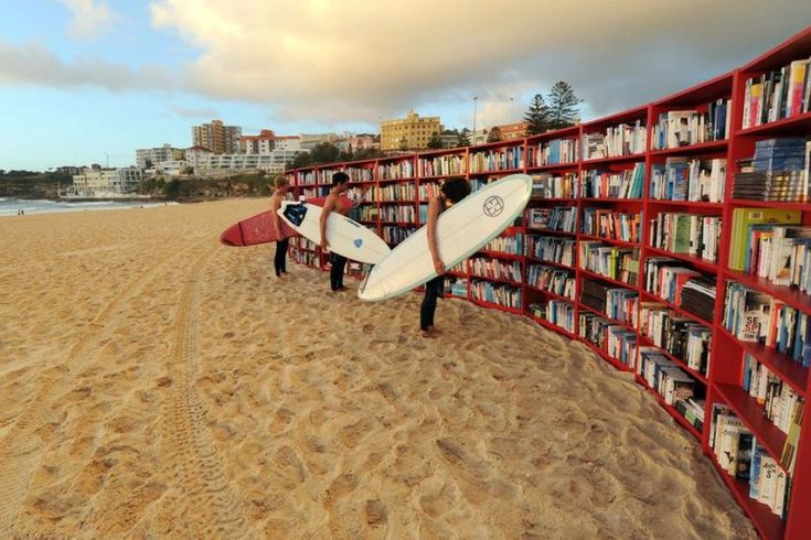 Surfers look at books on a set of 30 bookcases set up on Sydney's Bondi Beach - ABC News (Australian Broadcasting Corporation)