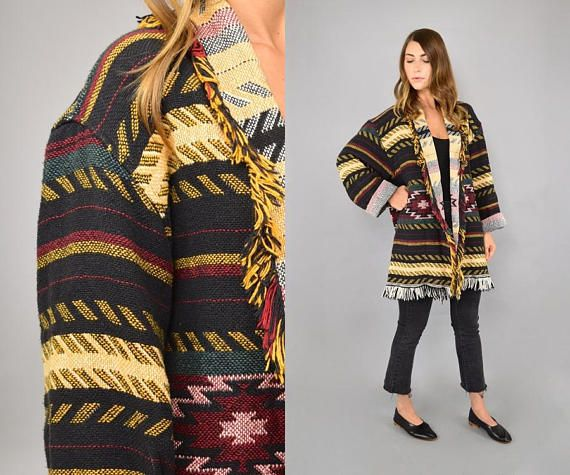 Vintage 80s southwestern tapestry blanket coat. Southwestern motif in burgundy, evergreen, goldenrod, and black. Features a slouchy fit, fringe trim, and an oversized fit. Designed to be worn open. Details → Era: 1980s Origin: USA Material: Cotton Care: Dry Clean Only Label: Wrapper