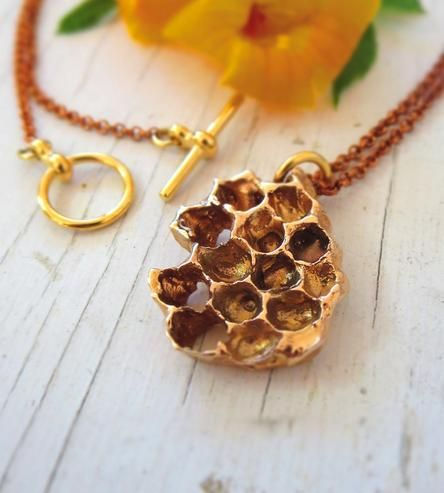 This honeycomb is cast in bronze (using the lost wax technique) from a real specimen. The honeycomb pendant is sculptural in nature, but it is also lightweight and comfortable. The casting is hung from a fine red brass chain and sealed to preserve its vibrancy.