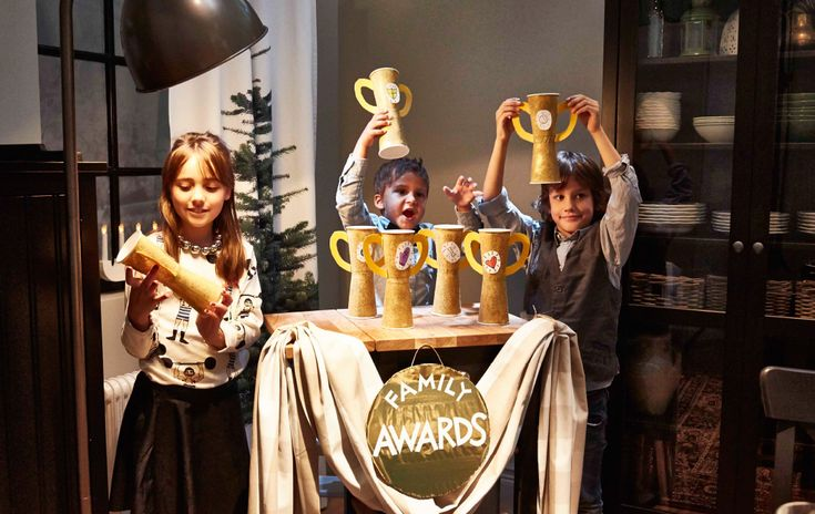 Två små pojkar och en flicka håller upp handgjorda priser. De står bakom ett tillfälligt podium i hörnet av ett rum.