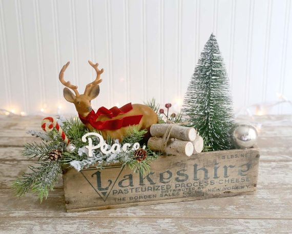 Unique en son genre, le style vintage, le folk art décoration de Noël tout en boîte de fromage vintage très grand. Cette boîte de fromage est remplie avec un cerf floqué vintage avec une ceinture de velours rouge, ornements argent vintage, un grand sapin, un lot de bois, beaucoup de branches couvertes de neige et d'un petit bonbon... oh et il y a une «paix» en bois. Les mesures de la boîte: 12 de long par 5 profond par 3 de haut. Y compris les bois du cerf, cette pièce est haute de 8½…