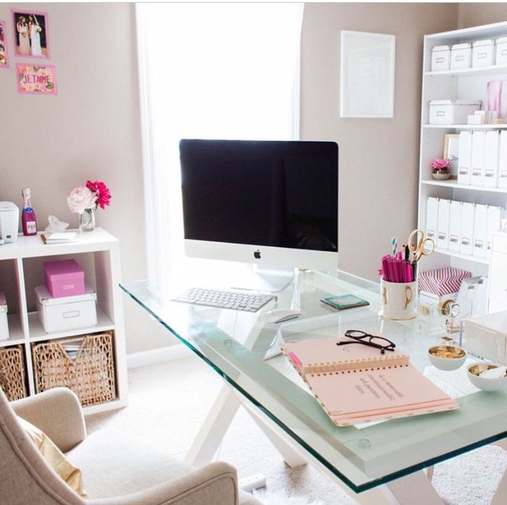 A bright and spacious creative home office complete with a glass desk and pink and white accessories