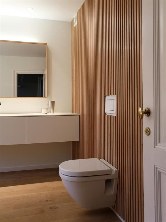 Very modern style toilets with a wooden wall and all the rest is white | Toilette blanc très moderne avec un mur en bois et tout le reste est blanc.