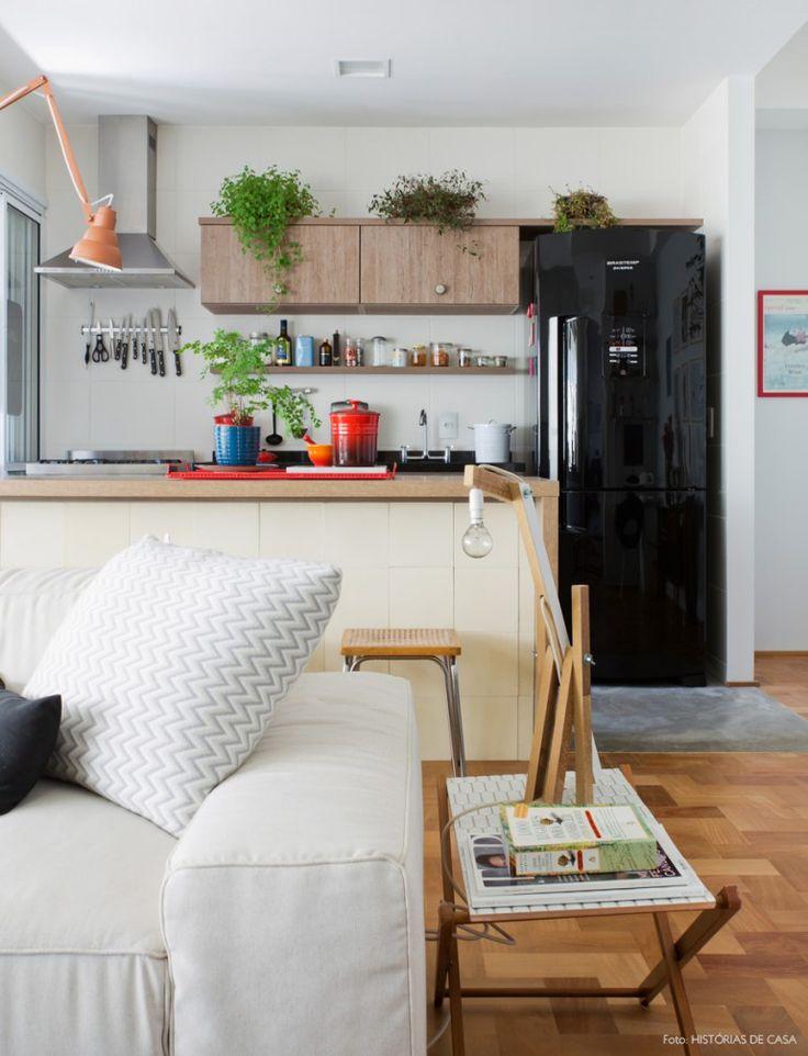Cozinha integrada com marcenaria clarinha, geladeira preta e muitas plantas.
