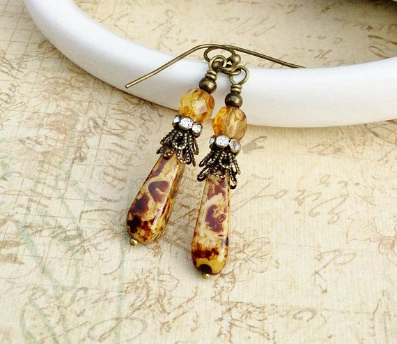 This is a lovely handcrafted pair of topaz and brown earrings. It combines Czech glass beads and crystals with antique gold accents to create a very unique piece of jewelry with a vintage appeal. This earring can be worn dressed up or down for any occasion. You will surely get