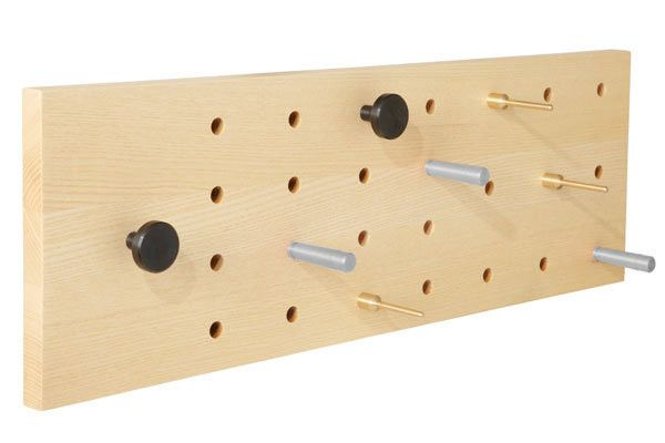Timberley coat rack  The Timberly hall rack is a neat little utilitarian design that evokes memories of simple wooden toys and childhood building blocks. The rack is wall-mounted and features a grid of holes, it comes with eight pegs in three different sizes that can be fitted into the grid in any configuration.  Available in solid ash or walnut with 2 steel, 3 aluminium and 3 brass movable pegs. Hall rack W 60 x H 20 x D 8.5 cm