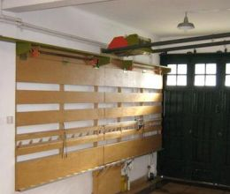 Panel Saw - Homemade panel saw constructed on a wood frame that rests flat against the wall when not in use. To enable sharing the space with an automobile, the saw carriage lifts up and is stored horizontally.