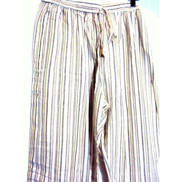 Pantalón hippie a rayas largo de algodón 100% natural hecho en Nepal. LLeva cuatro bolsillos, dos de ellos a medio muslo a los lados con cierre de botón de coco. Pantalón hippie de rayas de hombre o unisex en tonos gris y beige.