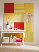 Telas revestidas com tecido formando um patchwork, nada melhor para esconder imperfeições nas paredes sem precisar pintar!