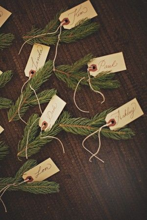 Easy place settings with spruce tigs and name written on tags with brown twine for a rustic feeling