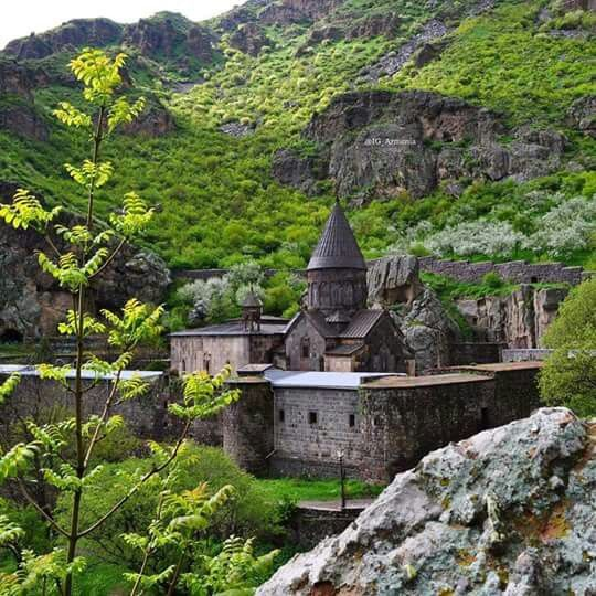 Geghard , a medieval monastery in the Kotayk province of Armenia, being partially carved out of the adjacent mountain, surrounded by cliffs. It is listed as a UNESCO World Heritage Site.