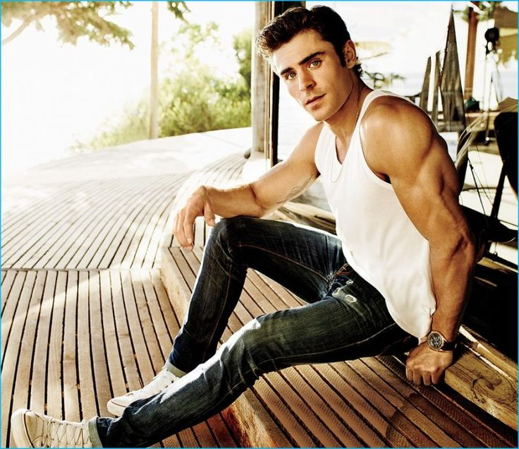 Zac Efron shows off his sculpted arms in a tank as he poses for Men's Fitness.
