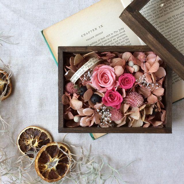 ダークブラウンに塗り込んだラスティック風の木箱。アンティークピンクのアジサイ、小花、木の実などをたくさん詰め込んだ、可愛らしいフラワーボックスです。蓋を開けて楽しむもよし、閉じて楽しむもよし。。。小さな宝箱のようなお花を楽しんでいただけたらと思います。※...