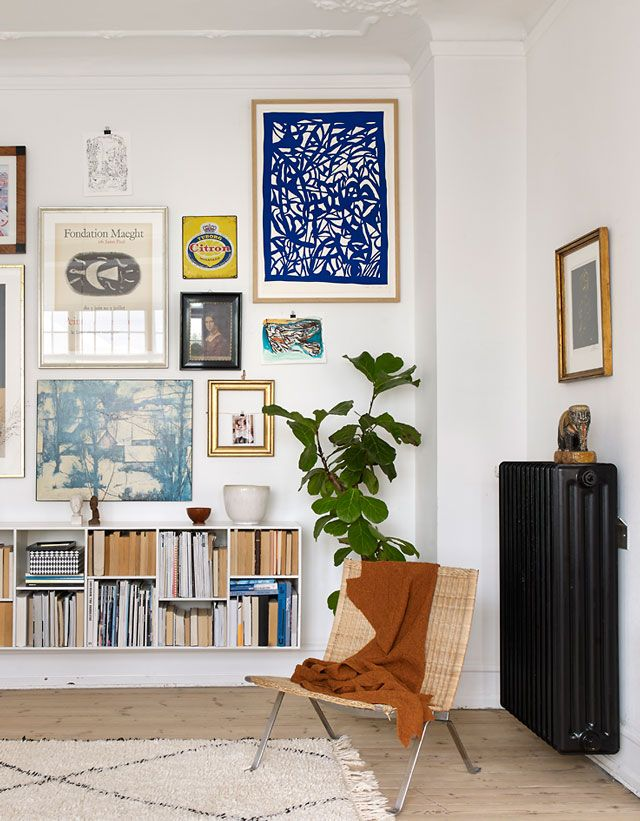 Love this eclectic gallery wall grouping - the unexpected addition of the deep blue work in the top right corner really makes it for us. And the way the houseplant was considered in the overall arrangement is stellar. A winner in our book!