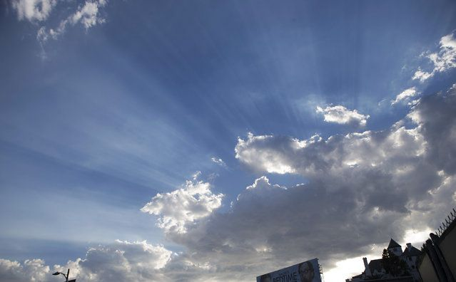 Sun rays are seen through a cloud formation in Los Angeles, California September 16, 2014. A heat wave continued Tuesday in Southern California with temperatures beyond 100 degrees Fahrenheit (38 degrees Celsius). (Photo by Mario Anzuoni/Reuters)