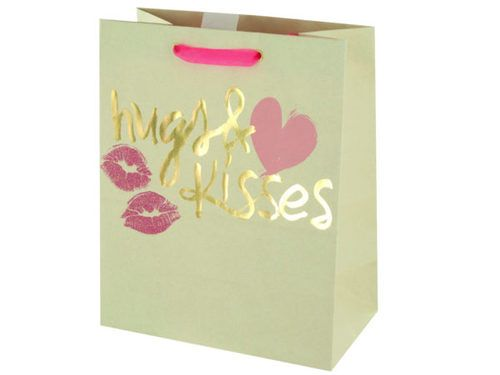 """Make someone smile with this Valentine's Hugs & Kisses Gift Bag featuring a matte cream paper bag with the words """"hugs & kisses"""" in gold foil, a heart, glitter lip prints and bright pink organza handles. Measures approximately 7.75"""" x 4.375"""" x 9.625"""". Comes loose."""