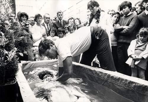 Along with several other Christian denominations, the Jehovah's Witness church believes in fully immersing new members during baptism. This 1971 photo shows minister M. Kingi baptising Mary Stevens of Porirua in a ceremony at the Lower Hutt town hall.