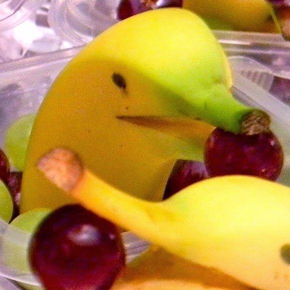 Dolphin banana holding grapes.