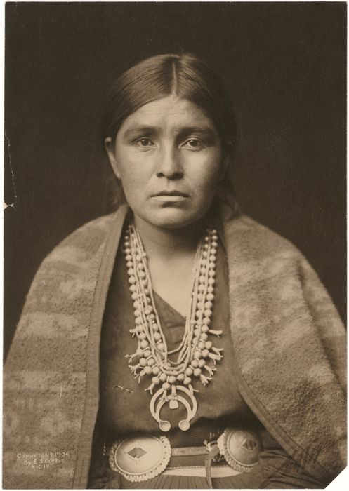 Portrait of a Navajo or Pueblo woman in traditional clothing, including a blanket, concho belt, and squash blossom necklace.   Arizona or New Mexico; USA (inferred