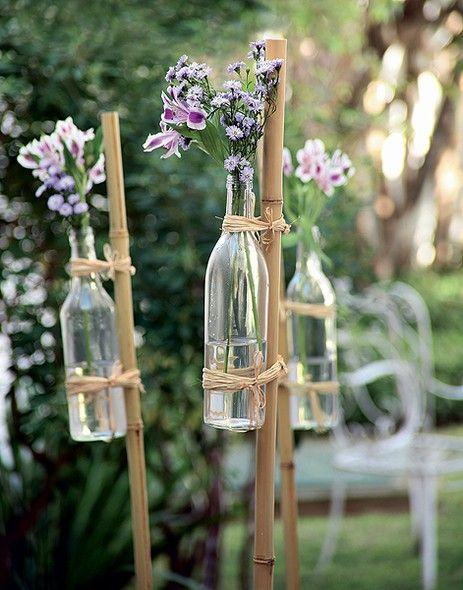 Flores em garrafas, fixadas em bambus por cordas/sisal, que são fincados no chão.