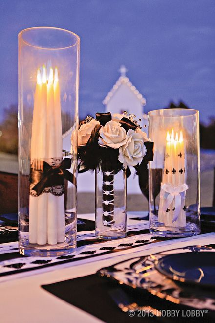 Simple white accessories take on a whole new style when you accent them with pops of dramatic black. Dot white taper candles with black fleur de lis brads (available in the Scrapbooking Department), or bundle them together with black lace and simple ribbon. And don't stop there. Transform a simple white rose bouquet with black feather clips, black ribbon and black diamond picks.