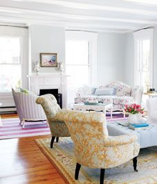 Living room  Every surface in the room is quiet and gentle: Pale blue-grey walls and accents offset creamy white-painted furniture. Vintage floral patterned fabrics and the armchairs, covered in a sunny toile, provide sweet pops of colour