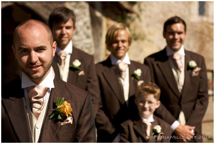 A groom with his best man and ushers on his wedding day. Brown suits, pinstripe trousers. Waistcoat and tails. Wedding style for men and groomsmen. Amber flowers
