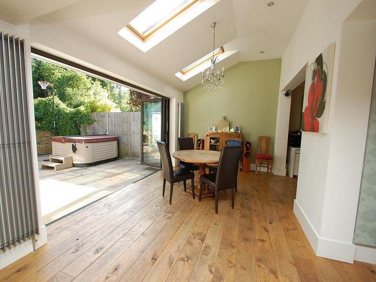 photo of beige white kitchen with sliding folding doors vertical radiator hardwood floor