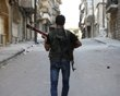 A Free Syrian Army fighter plays a guitar as he walks through a street near Aleppo