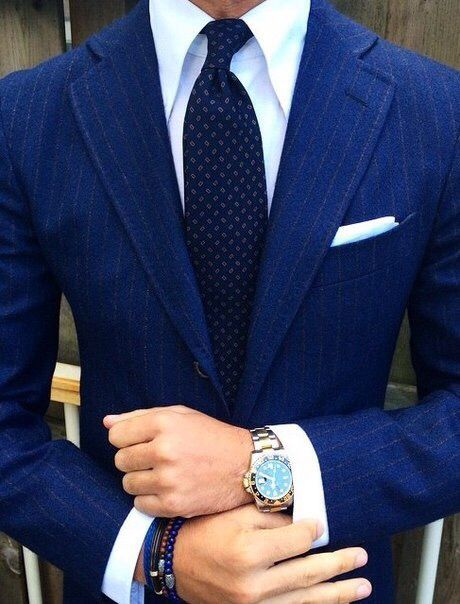 Stripped blue suit, patterned blue tie, white shirt and handkerchief, Rolex and beads