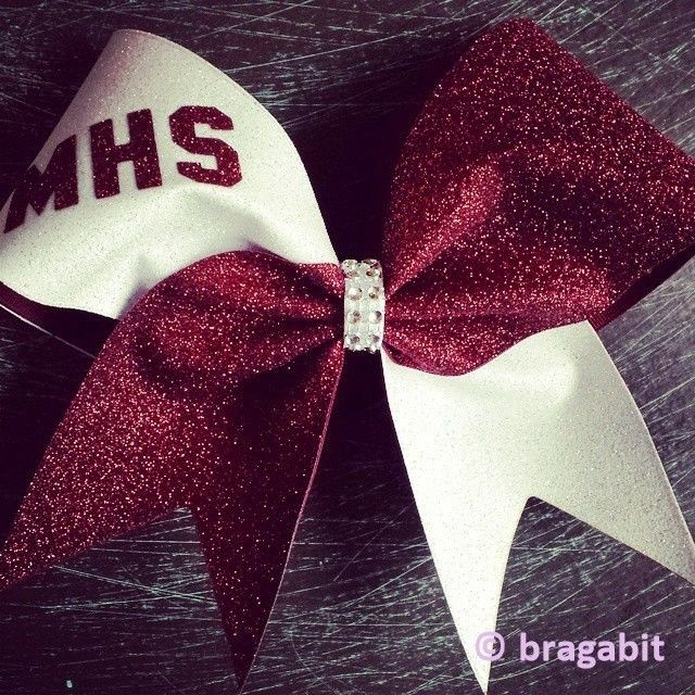 Two color glitter bow. Maroon and white glitter cheer bow with rhinestone material center.