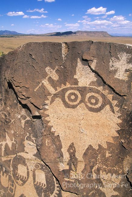 A dramatic wide-eyed shield man occupies a spot high on a volcanic ridge overlooking the Galesteo River Basin near the village of Galesteo, New Mexico, a few miles from Santa Fe.  Photo by Charles Mann