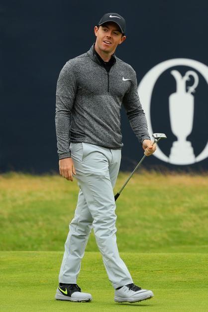 Rory McIlroy wearing Nike Lunar Control 4 Golf Shoes, Nike Modern Tech Woven Golf Pants in Wolf Grey, Nike Flex Knit Half Zip Golf Shirt in Black/Black/Flat Silver, Nike Classic 99 Fitted Golf Hat and Nike Method Origin Golf Putter