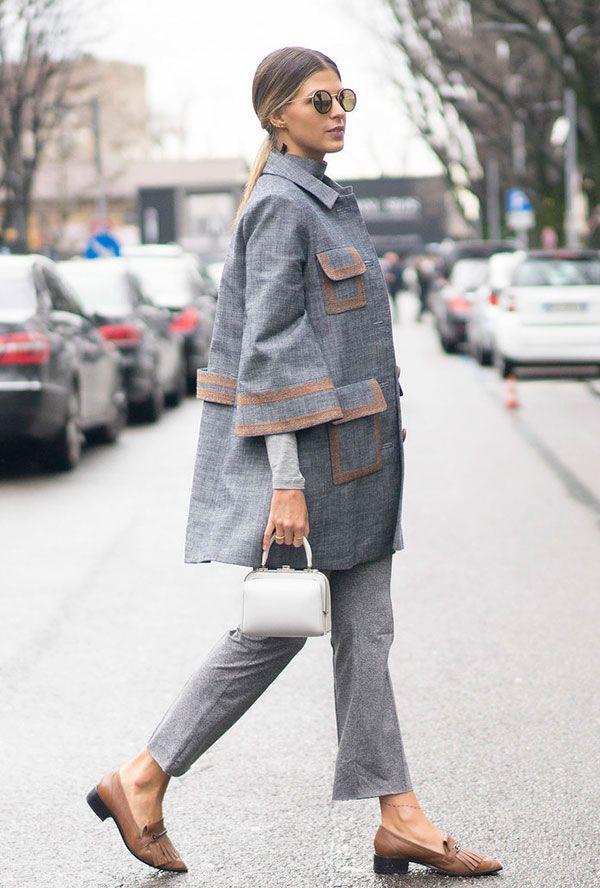 Street style look Anna Fasano usando conjunto alfaiataria blazer e calça cinza, flat bege, bolsa de mão branca e óculos redondo.