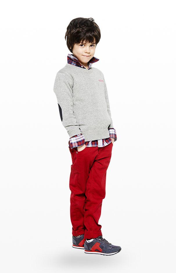 Preppy Boy ! Pour un look de rentrée sans faute cette tenue pour garçon composée d'une chemise à carreaux, d'un pull gris avec coudières contrastées et d'un pantalon rouge uni. Une tenue à porter avec des baskets colorées pour une allure pile dans la tendance.