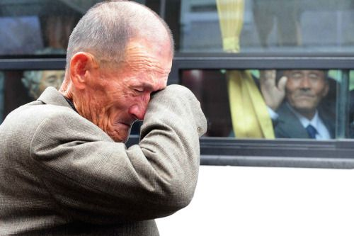 """mianoti:  """" Photos of 2010:  A North Korean man (right) on a bus waves his hand as a South Korean man weeps after a luncheon meeting during inter-Korean temporary family reunions at Mount Kumgang resort October 31, 2010. Four hundred and thirty-six..."""