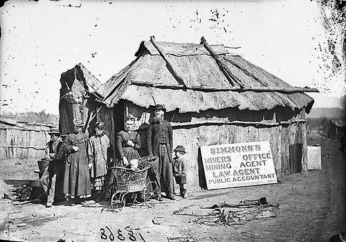Simmons' (miners' office, mining agent, law agent and public accountant) and family outside his bark hut, Gulgong area, 1871-1875 / American & Australasian Photographic Company
