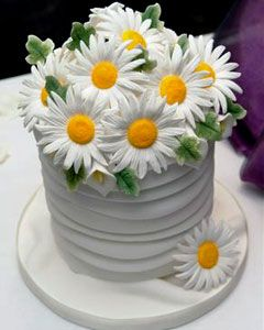 Simply adorable small white fondant wedding cake decorated with white hand crafted gum paste daisies as the wedding cake topper