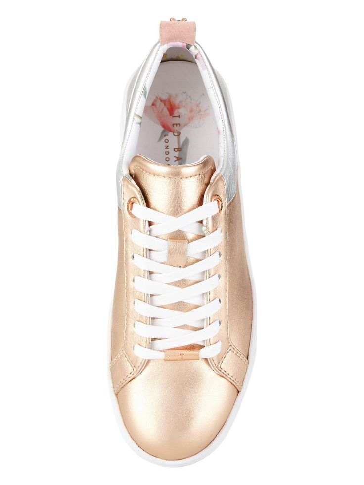 Ted Baker Metallic Trainers Take a sartorial step this summer in these Kulei metallic trainers by Ted Baker! Designed with metallic panels to give them all the futuristic feels and in a low top style with suede accents you'll love how they master sports luxe without even trying!Team them with everything this summer, from your shorts and dresses to your jeans and tailored trews - anything goes with Kulei.Metallic trimRubber soleLace up fasteningTed Baker brandedLining: Leather/Textile...