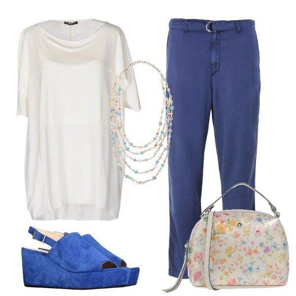 Per dare un tocco in più alla semplice tunica bianca e i morbidi pantaloni blu alla caviglia, bastano i sandali con zeppa, la piccola borsa con piccoli fiori multicolor come la leggera collanina.