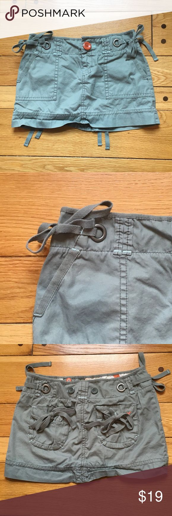 """American Eagle Outfitters Chino Style Mini Skirt Excellent condition. Chino style green khaki mini skirt with accent ties on both hips and both back pockets. Two front slant pockets. 100% cotton. When flat, waist measures approx. 14.5"""" across and 12"""" from top to bottom. American Eagle Outfitters Skirts Mini"""