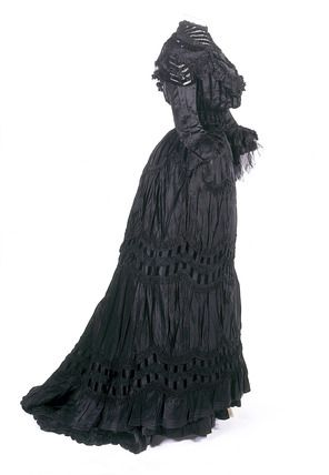 Black silk dress (bodice, skirt, and underskirt), made by Irma Cescotti, Italian, 1905-08. The bodice and skirt are trimmed with ruched organza and narrow black cotton velvet ribbon. Cescotti moved to London in about 1900 and found work in a family household. In 1905, she married Pietro Cocco, an Italian shoemaker and repairer with a business at 418 Portobello Road.