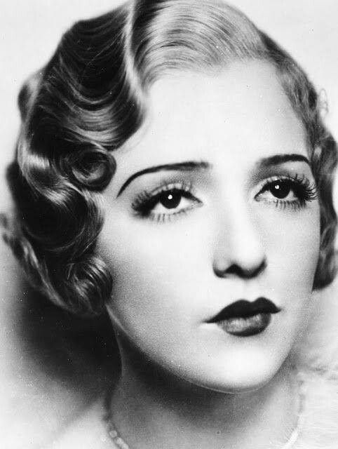 A true 1920s makeup. The thin brows with the heavy eye and mouth seemed to be the go to look of the decade with the heart shaped lips with the doe eyes