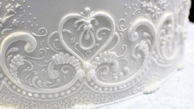 Learn how to pipe lace patterns effectively on the vertical surfaces around the cake.