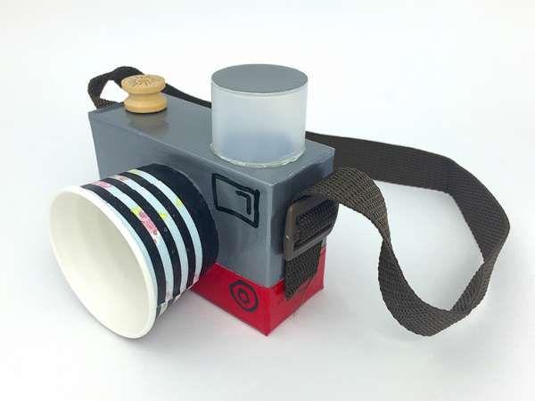 Réalisez un appareil photo en carton pour vos enfants avec seulement une boite en carton, un gobelet, un couvercle en plastique, une bobine et un ruban ou une vieille ceinture.